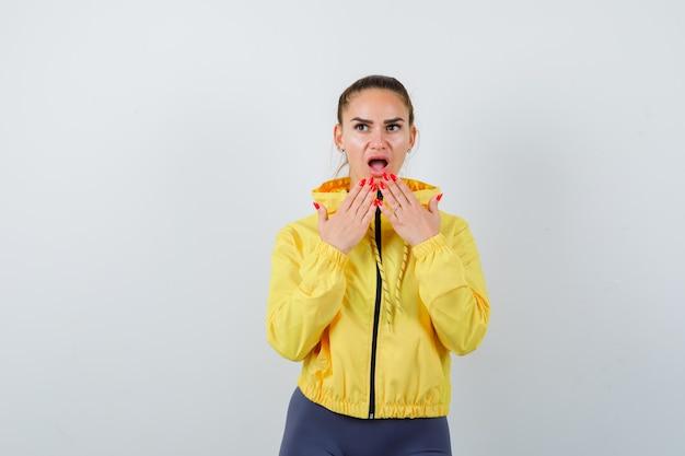 Młoda dama w żółtej kurtce z rękami blisko ust i patrząc zdziwiony, widok z przodu.