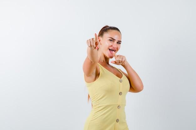 Młoda dama w żółtej sukience, wskazując na aparat i patrząc błogi, widok z przodu.
