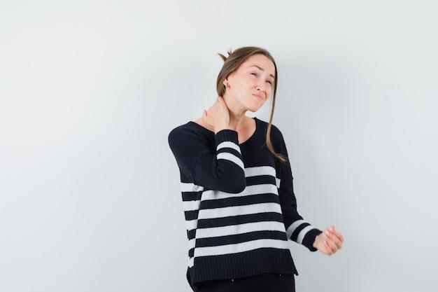 Młoda dama w zwykłej koszuli cierpi na ból szyi i wygląda na zmęczoną