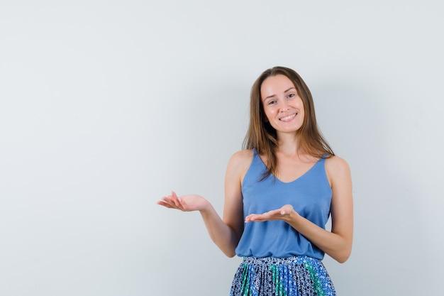 Młoda dama witająca lub pokazująca coś w podkoszulku, spódnicy i wyglądająca wesoło. przedni widok.