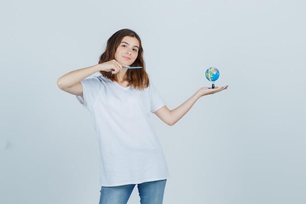 Młoda dama wskazując kulę ziemską piórem, trzymając w t-shirt, dżinsy i patrząc pewnie. przedni widok.