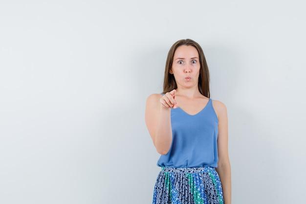 Młoda dama, wskazując na aparat, jednocześnie wydymając usta w bluzce, spódnicy i patrząc niespokojnie. przedni widok.