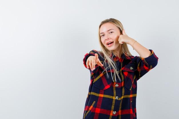 Młoda dama, wskazując na aparat, pokazując kciuk w kraciastej koszuli i wyglądający na zdumionego. przedni widok.