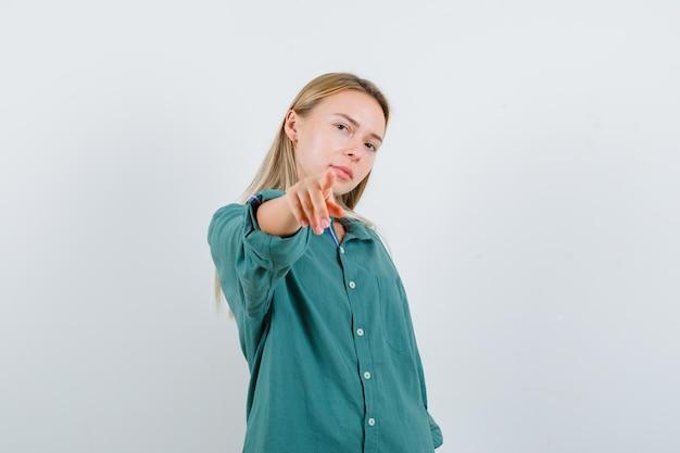 Młoda dama, wskazując na aparat w zielonej koszuli i patrząc pewnie.