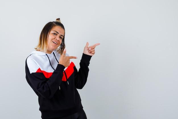 Młoda dama wskazując na bok w sweter z kapturem i patrząc radosny.