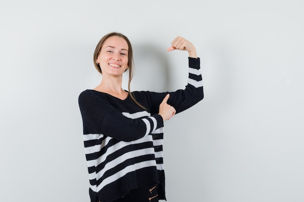 Młoda dama, wskazując na jej mięśnie w przypadkowej koszuli i wyglądająca na szczęśliwą