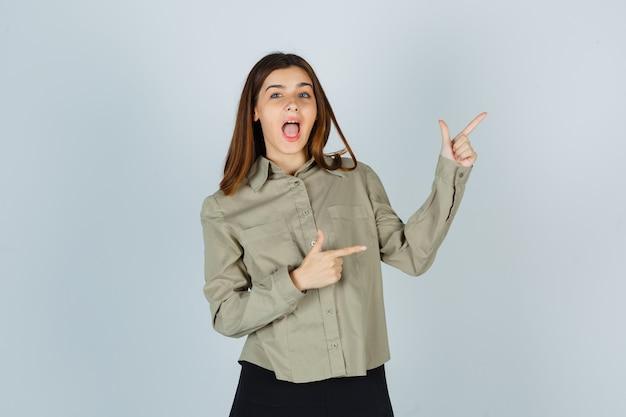 Młoda dama wskazując na prawy górny róg w koszuli, spódnicy i wygląda na szczęśliwą. przedni widok.