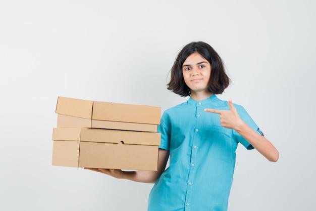 Młoda dama wskazując na pudełka w niebieskiej koszuli i patrząc na gotowe.