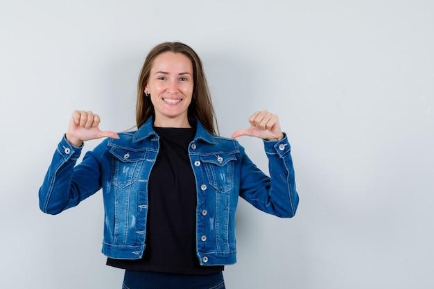 Młoda dama wskazując na siebie kciukami w bluzce, kurtce i patrząc dumny, widok z przodu.