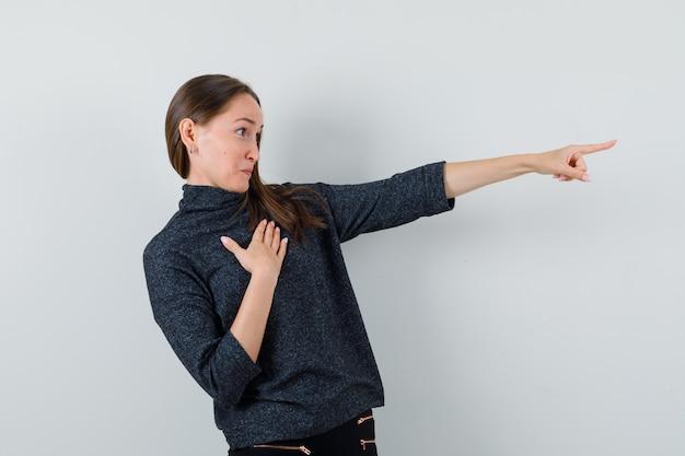 Młoda dama wskazując w koszuli i patrząc zaciekawiony