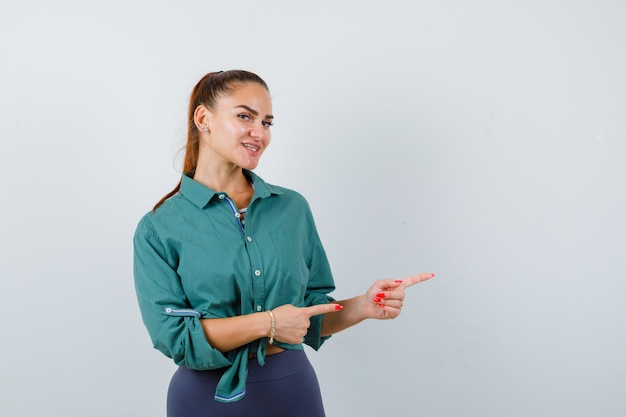Młoda dama wskazując w zieloną koszulę i patrząc wesoło. przedni widok.