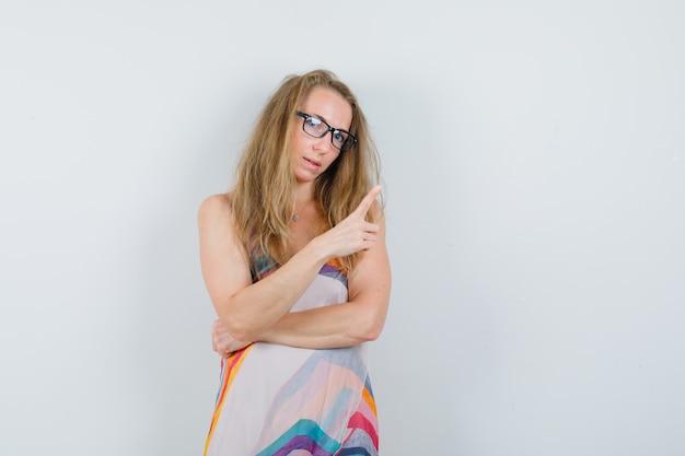 Młoda dama, wskazując z boku z palcem w letniej sukience
