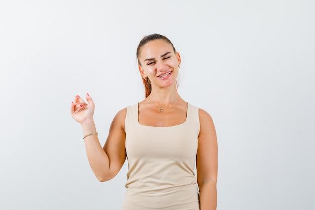 Młoda dama wskazująca do tyłu, mrugająca okiem w podkoszulku i wyglądająca wesoło. przedni widok.