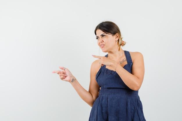 Młoda dama wskazująca na bok w sukience