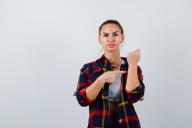 Młoda dama wskazująca na jej ramię uniesione w górę, koszulę w kratę i wyglądająca poważnie, widok z przodu.