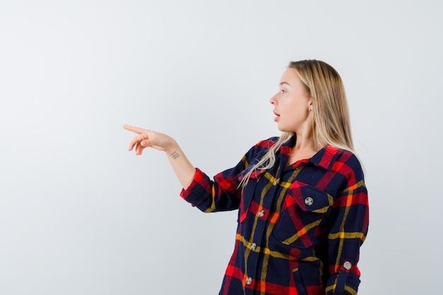 Młoda dama wskazująca na lewą stronę w koszuli w kratę i wyglądająca na zdumioną. przedni widok.