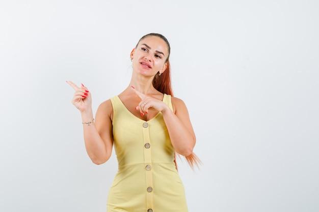 Młoda dama wskazująca na lewy górny róg w żółtej sukience i zamyślona. przedni widok.