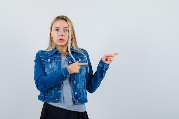 Młoda dama wskazująca na prawą stronę w koszulce, dżinsowej kurtce, spódnicy i patrząc zdumiona.