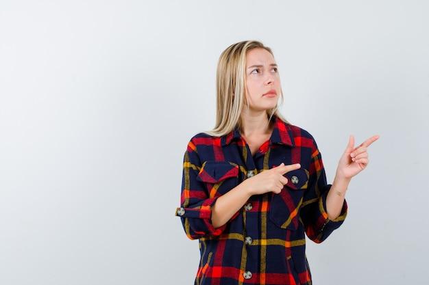 Młoda dama wskazująca na prawą stronę w kraciastej koszuli i wyglądająca na zamyśloną, widok z przodu.