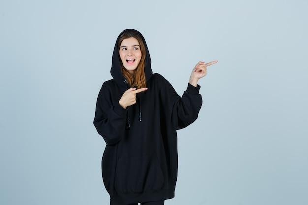 Młoda dama wskazująca na prawą stronę w obszernej bluzie z kapturem, spodniach i wyglądająca błogo, widok z przodu.