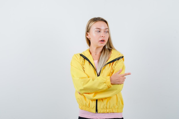 Młoda dama wskazująca na prawą stronę w t-shircie, kurtce i wyglądająca na zdziwioną