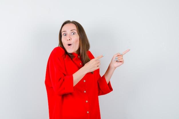 Młoda dama wskazująca na prawy górny róg w czerwonej bluzce i patrząca zdziwiona, widok z przodu.