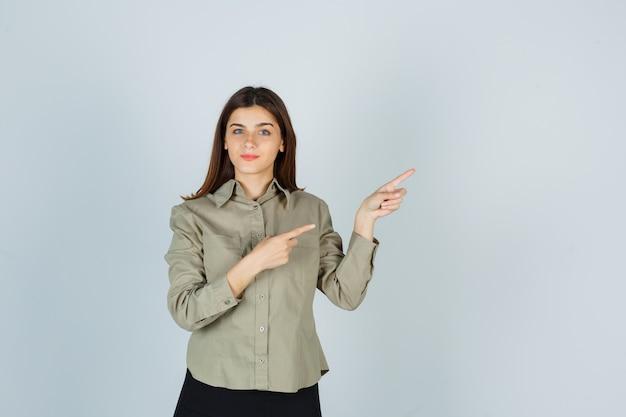 Młoda dama wskazująca na prawy górny róg w koszuli, spódnicy i wyglądająca na zadowoloną