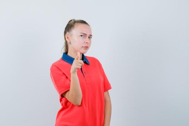 Młoda dama wskazująca na przód w koszulce i wyglądająca podejrzanie