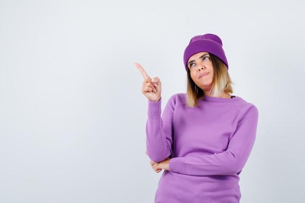 Młoda dama wskazująca w fioletowy sweter, czapka i wyglądająca na zadowoloną. przedni widok.