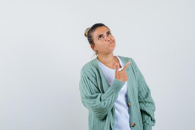 Młoda dama wskazująca w koszulce, kurtce i wyglądająca na zamyśloną