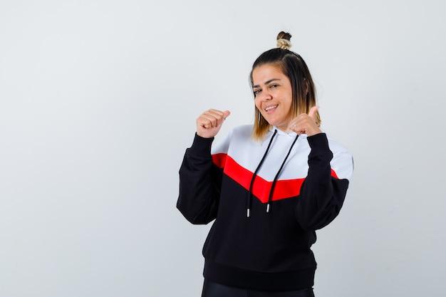Młoda dama wskazuje kciukami w sweter z kapturem i wygląda na szczęśliwą.