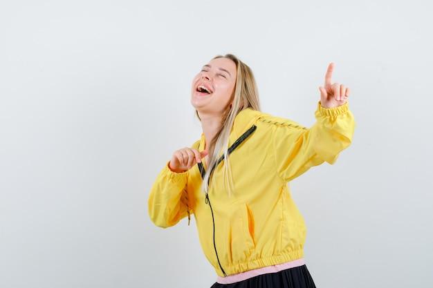 Młoda dama wskazuje na bok w koszulce, kurtce i wygląda optymistycznie