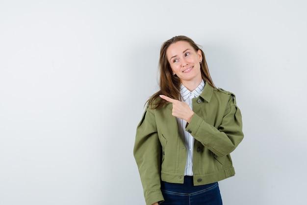 Młoda dama wskazuje na lewą stronę w koszuli, kurtce i wygląda uroczo, widok z przodu.