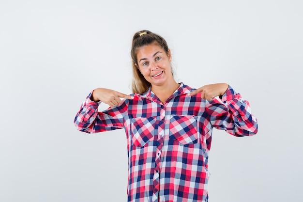 Młoda dama wskazuje na siebie w kraciastej koszuli i wygląda dumnie. przedni widok.