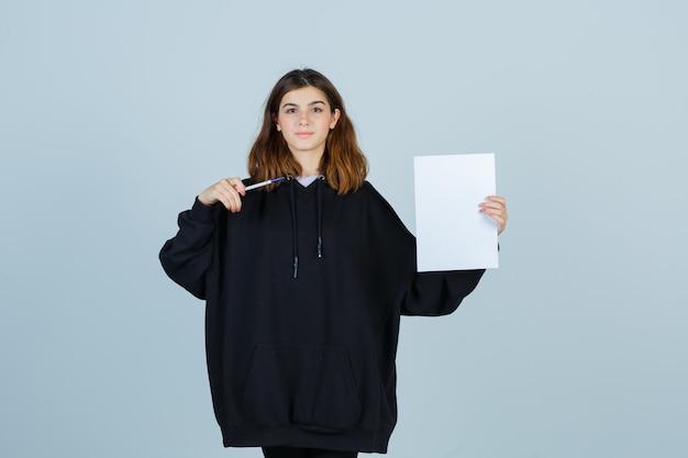 Młoda dama wskazuje papier z piórem w obszernej bluzie z kapturem, spodniach i wygląda pewnie, widok z przodu.