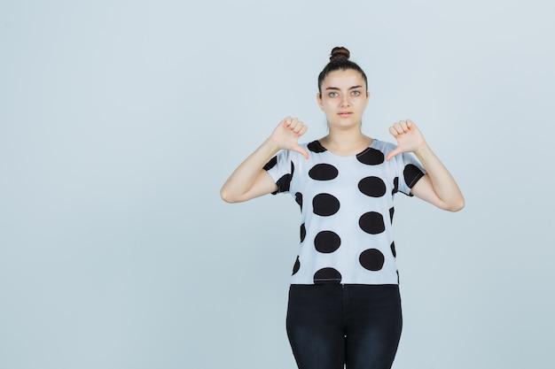 Młoda dama wskazuje się kciukami w t-shirt, dżinsy i wygląda dumnie, widok z przodu.