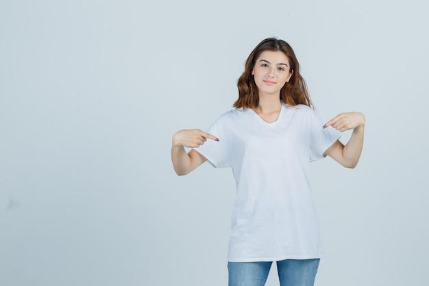 Młoda dama wskazuje się w t-shirt, dżinsy i wygląda dumnie, widok z przodu.