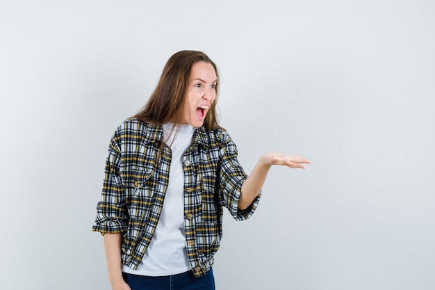 Młoda dama wyciągając rękę w pytającym geście w t-shirt, kurtce, dżinsach i patrząc zły, widok z przodu.