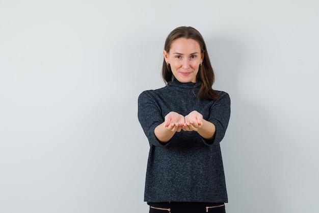Młoda dama wyciągając złożone dłonie w koszuli i patrząc wesoło