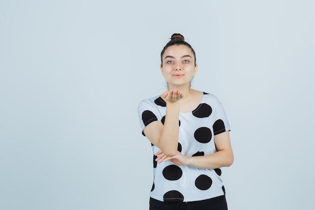 Młoda dama wysyłająca buziaka ręką w koszulce, dżinsach i ładnie wyglądająca, widok z przodu.