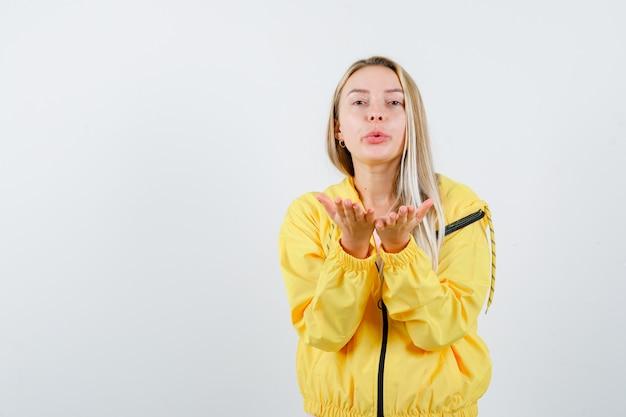 Młoda dama wysyłająca buziaka ręką w koszulce, kurtce i słodko wyglądająca