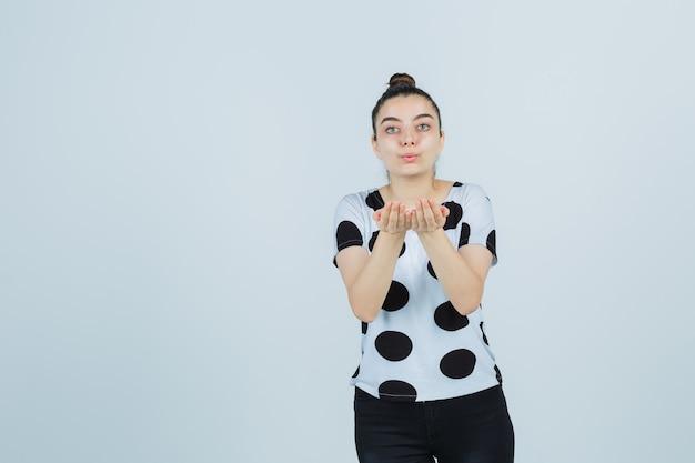 Młoda dama wysyłająca buziaka z rękami w koszulce, dżinsach i wyglądająca uroczo, widok z przodu.