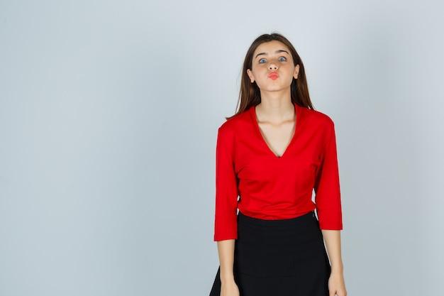 Młoda dama wysyłająca buziaka z wydymonymi ustami w czerwonej bluzce, spódniczce i ładnie wyglądająca