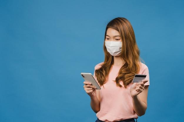Młoda dama z azji nosząca maskę medyczną za pomocą telefonu i karty kredytowej z pozytywnym wyrazem twarzy, uśmiecha się szeroko, ubrana w zwykłą odzież i stoi na białym tle na niebieskiej ścianie