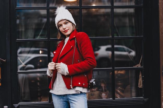 Młoda dama z czerwoną szminką i brązowymi oczami ubrana w jasny płaszcz i biały kapelusz pozuje z aparatem retro przed oknem.