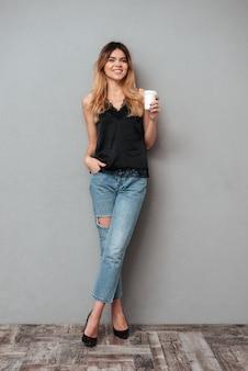 Młoda dama z filiżanki kawy pozować odizolowywam