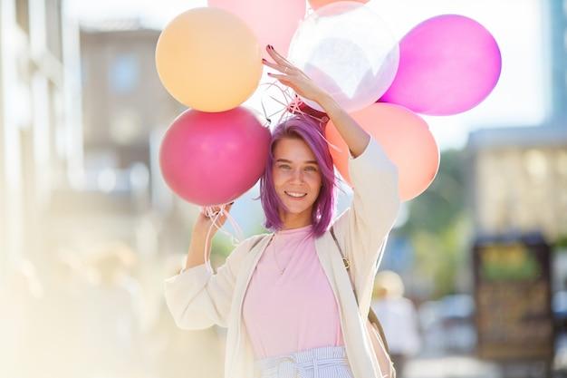 Młoda dama z fioletowymi włosami stojący na ulicy miasta z bukietem balonów