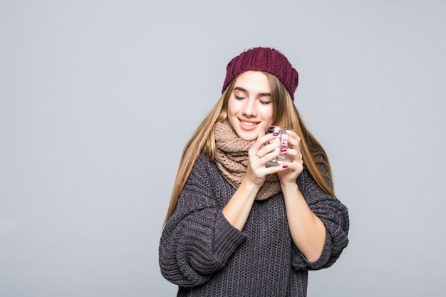 Młoda dama z grypą i zimnymi napojami gorący napój ziołowy tee, aby stać się zdrowym na szarym