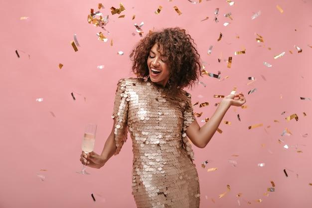 Młoda dama z krótkimi włosami brunetki w błyszczącej stylowej sukience pozuje z kieliszkiem z winem i konfetti na izolowanej ścianie...