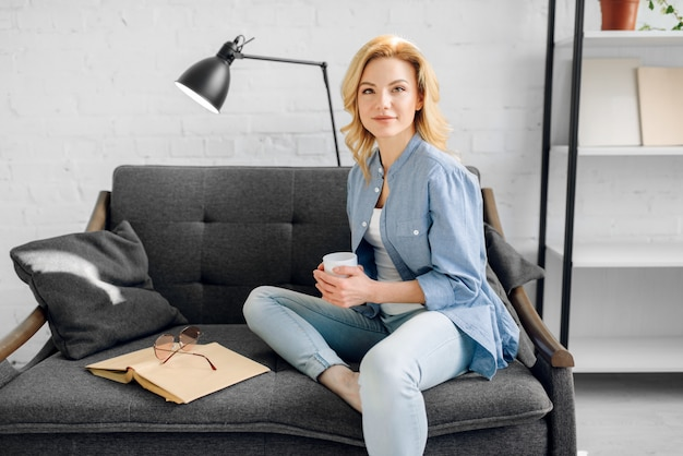 Młoda dama z książką i filiżanką kawy pozuje na przytulnej czarnej kanapie, salon w odcieniach bieli